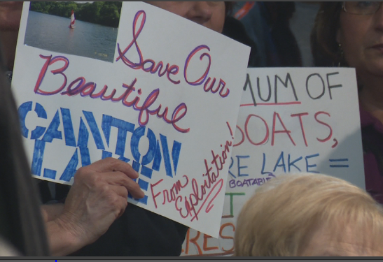 Signs encouraging council to save Canton Lake during council meeting