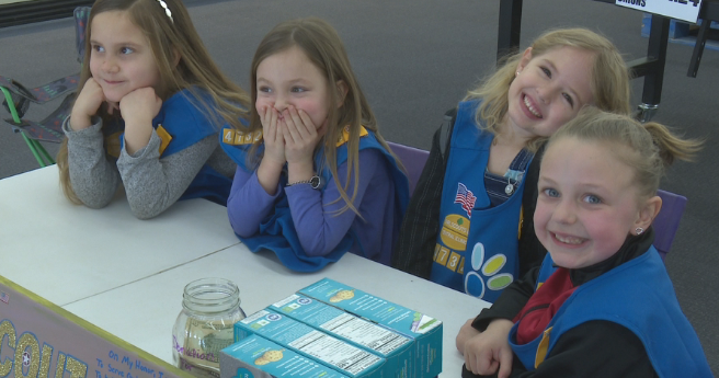 Girl Scouts all smiles as they sell cookies for soldiers