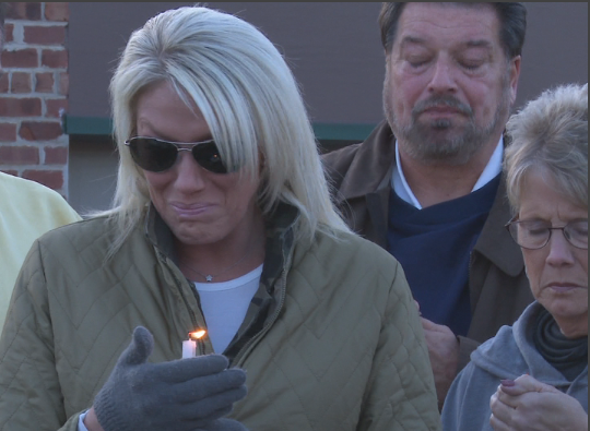 Jenni McGruder's sister sheds tears while holding a candle in her honor