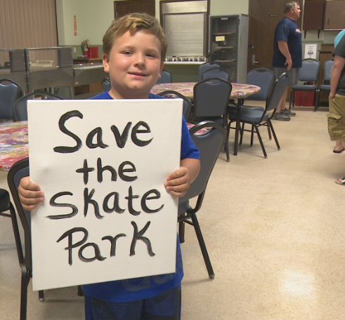 Young skate park supporter displays his sign proudly
