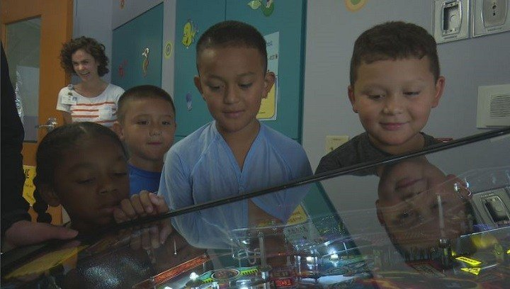 These children surge around their new pinball machine, part of Project Pinball to help kids recover during hospital stays.